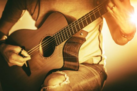 Photo for Musician with Guitar Playing Some Music. Acoustic Guitar String Instrument in Hand of Caucasian Men - Royalty Free Image