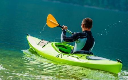 Foto de Viaje recreativo en kayak. Hombres caucásicos en el kayak en el lago escénico . - Imagen libre de derechos