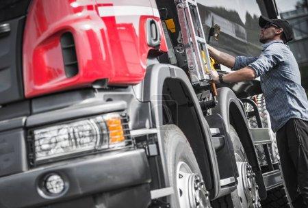 Photo pour Vérifier la charge finale du conducteur de camion caucasien avant de prendre la route. Thème Transport lourd . - image libre de droit