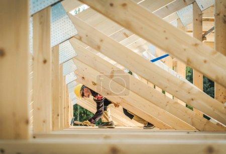 Photo pour Construction à ossature de maison en bois. Entrepreneur caucasien dans la trentaine portant un chapeau dur. Construction résidentielle . - image libre de droit