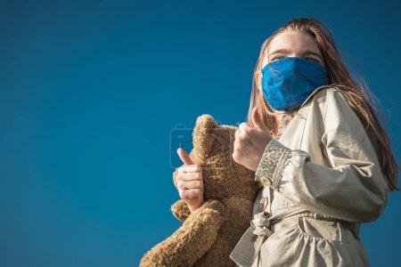 Photo pour Covid 19 Pandemia Theme. fille caucasienne en bleu visage masque tenant grand ours en peluche montrant pouces au cours de l'épidémie mondiale de virus . - image libre de droit