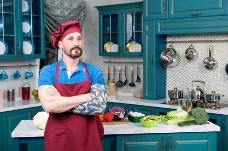 Photo pour Barbu Chef rêve avec tatoués et traversé la main à la cuisine. Cuire au tablier rouge et bonnet rouge se tenant debout sur cuisine. Beau mec en face de la table avec des légumes - image libre de droit