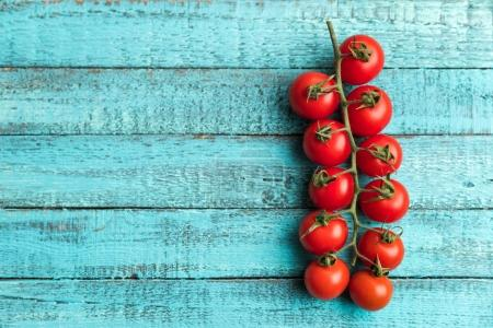 Photo for Cherry tomatoes on turquoise wooden table top texture. fresh seasonal vegetables concept - Royalty Free Image