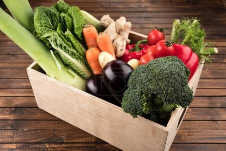 Photo for Fresh seasonal vegetables in wooden box on wooden table background - Royalty Free Image