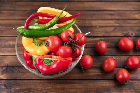 Photo for Cherry tomatoes and peppers in bowl on wooden table top texture. fresh seasonal vegetables concept - Royalty Free Image