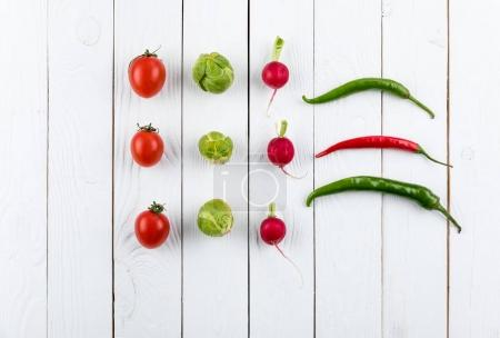 Photo for Different fresh seasonal vegetables in rows on white rustic wooden background - Royalty Free Image