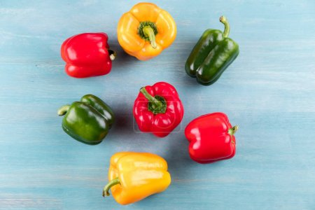Top view of fresh ripe peppers on blue wooden tabl...