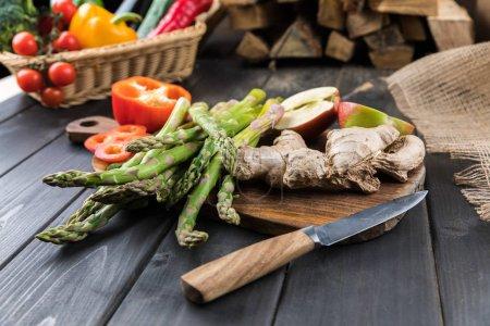 Photo pour Vue rapprochée des légumes de saison frais et des pommes coupées en deux sur un plateau en bois - image libre de droit