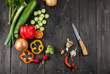 Photo for Top view of fresh seasonal vegetables and knife on wooden table background - Royalty Free Image