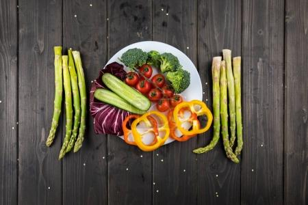 Photo for Close-up top view of fresh vegetables on plate on rustic wooden background - Royalty Free Image