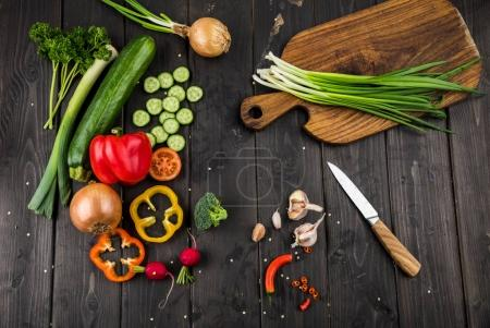 Photo for Top view of fresh seasonal vegetables and knife on rustic wooden background - Royalty Free Image