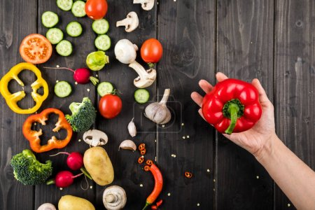 Photo for Top view of hand holding pepper and fresh vegetables on wooden table background - Royalty Free Image