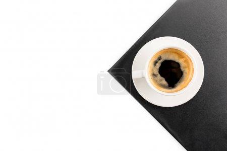 Photo pour Vue du dessus de tasse de café expresso sur serviette noire isolée blanche sur fond avec espace de copie - image libre de droit