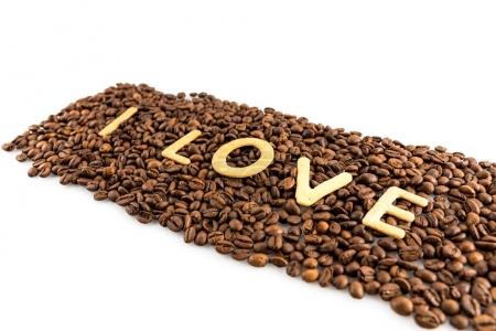 Photo for Coffee beans with cookies in shape of Love word isolated on white - Royalty Free Image