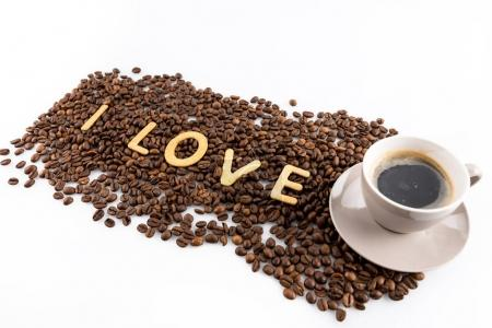 Photo for Cup of coffee and coffee beans with cookies in shape of Love word isolated on white - Royalty Free Image
