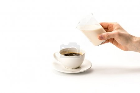 Photo for Person pouring milk into cup of coffee isolated on white background - Royalty Free Image