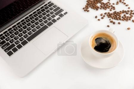Photo for Close-up view of laptop, cup of fresh coffee and coffee beans isolated on white - Royalty Free Image