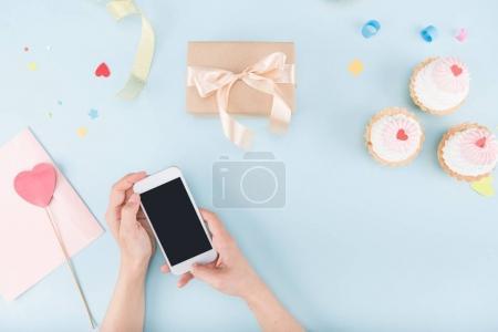 manos sosteniendo smartphone con pasteles