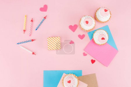 Photo for Top view of delicious cupcakes, colorful candles and hearts symbols on pink, birthday party concept - Royalty Free Image