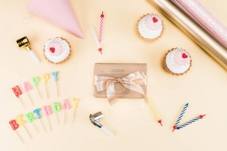 Photo for Top view of happy birthday lettering, envelope with ribbon, cakes and colorful cards on pink, birthday party concept - Royalty Free Image