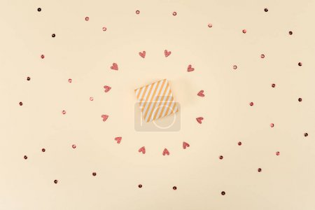 Photo for Top view of gift box and confetti isolated on beige, birthday party concept - Royalty Free Image
