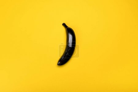 Photo for Top view of black colored banana isolated on yellow, colorful background - Royalty Free Image