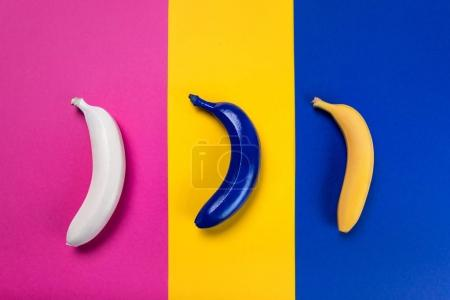 Photo for Close-up view of white, blue and yellow bananas isolated on pink, yellow and blue - Royalty Free Image