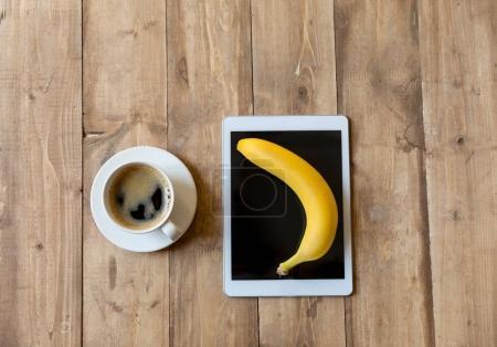 Foto de Vista superior de banano maduro fresca y tableta digital en la superficie de madera - Imagen libre de derechos
