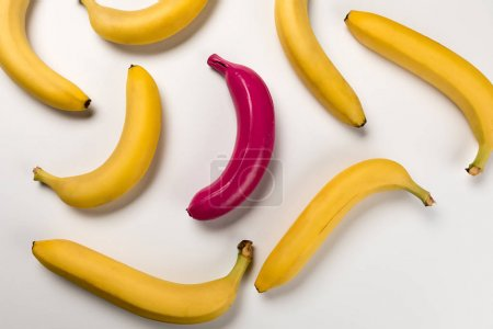 Photo for Top view of yellow ripe bananas and pink one isolated on pink - Royalty Free Image