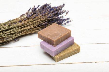Photo pour Vue rapprochée du tas de savon fait maison avec bouquet de lavande séchée sur une surface en bois - image libre de droit