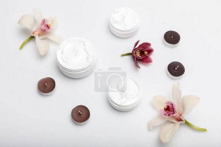 Photo for Close-up view of organic cream in containers with orchids and candles isolated on white - Royalty Free Image