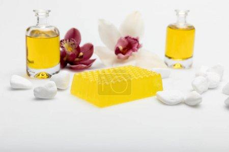Photo pour Vue rapprochée du savon de miel fait maison avec huiles essentielles et orchidées isolées sur blanc - image libre de droit