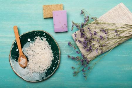 Photo pour Vue de dessus des fleurs de lavande séchées avec sel de mer et savon fait à la main sur une surface en bois bleu - image libre de droit