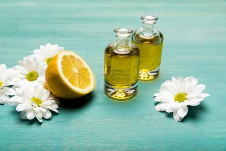 Photo pour Vue rapprochée de l'huile essentielle en bouteilles avec tranches de citron et camomille sur table en bois bleue - image libre de droit