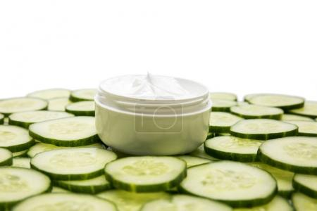 Photo for Close-up view of facial cream in container and cucumber slices isolated on white - Royalty Free Image