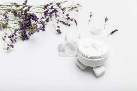 Photo for Close-up view of organic cream in container and dried lavender isolated on white - Royalty Free Image