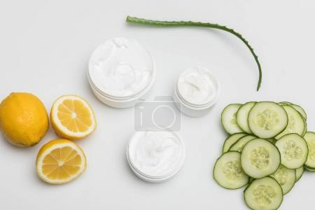 Photo for Top view of facial cream in containers, cucumber and lemon slices and aloe vera plant  isolated on white - Royalty Free Image
