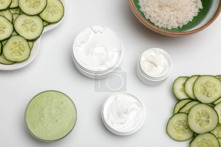 Photo for Top view of facial cream in containers and cucumber slices isolated on white - Royalty Free Image
