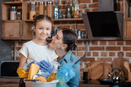 Photo for Portrait of happy mother and daughter in rubber gloves with cleaning supplies - Royalty Free Image