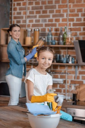 Photo for Smiling girl in rubber gloves with cleaning supplies and mother behind in kitchen - Royalty Free Image