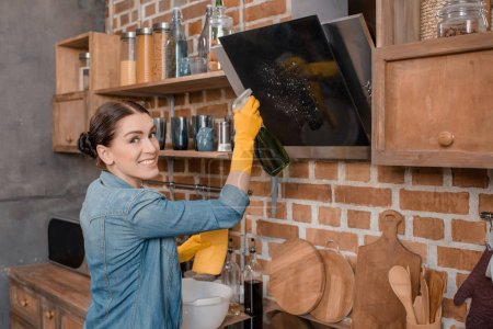 Photo for Side view of smiling housewife in rubber gloves cleaning tv set at home - Royalty Free Image