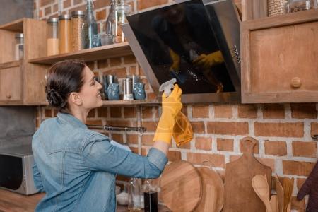 Photo pour Vue latérale de la ménagère souriante en gants de caoutchouc nettoyage tv à la maison - image libre de droit