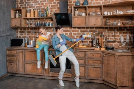Photo for Daughter singing and mother pretending playing on wisp in kitchen - Royalty Free Image