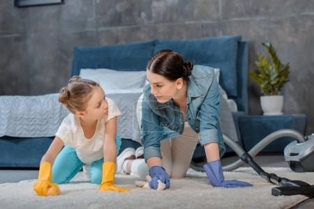 Mother and daughter cleaning carpet