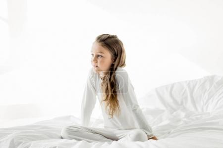 Photo for Adorable little girl in white sleepwear sitting on bed at home  isolated on white - Royalty Free Image