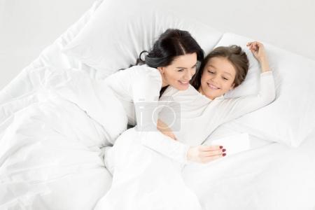 Photo pour Adorable fille et mère prenant selfie sur smartphone tout en étant couché sur le lit isolé sur blanc - image libre de droit