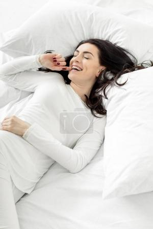 Photo for Attractive woman in white sleepwear awakening in bed at home - Royalty Free Image