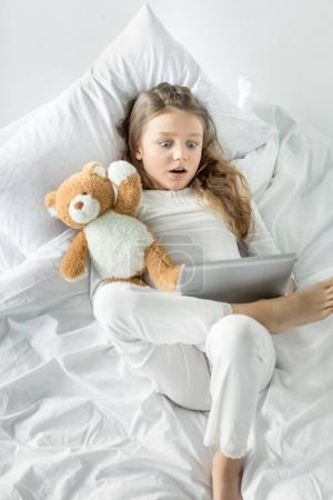 Girl with digital tablet in bed