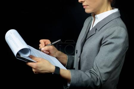 Businesswoman signing papers