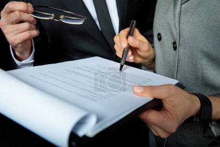 Photo for Close-up partial view of businesspeople discussing and signing papers - Royalty Free Image